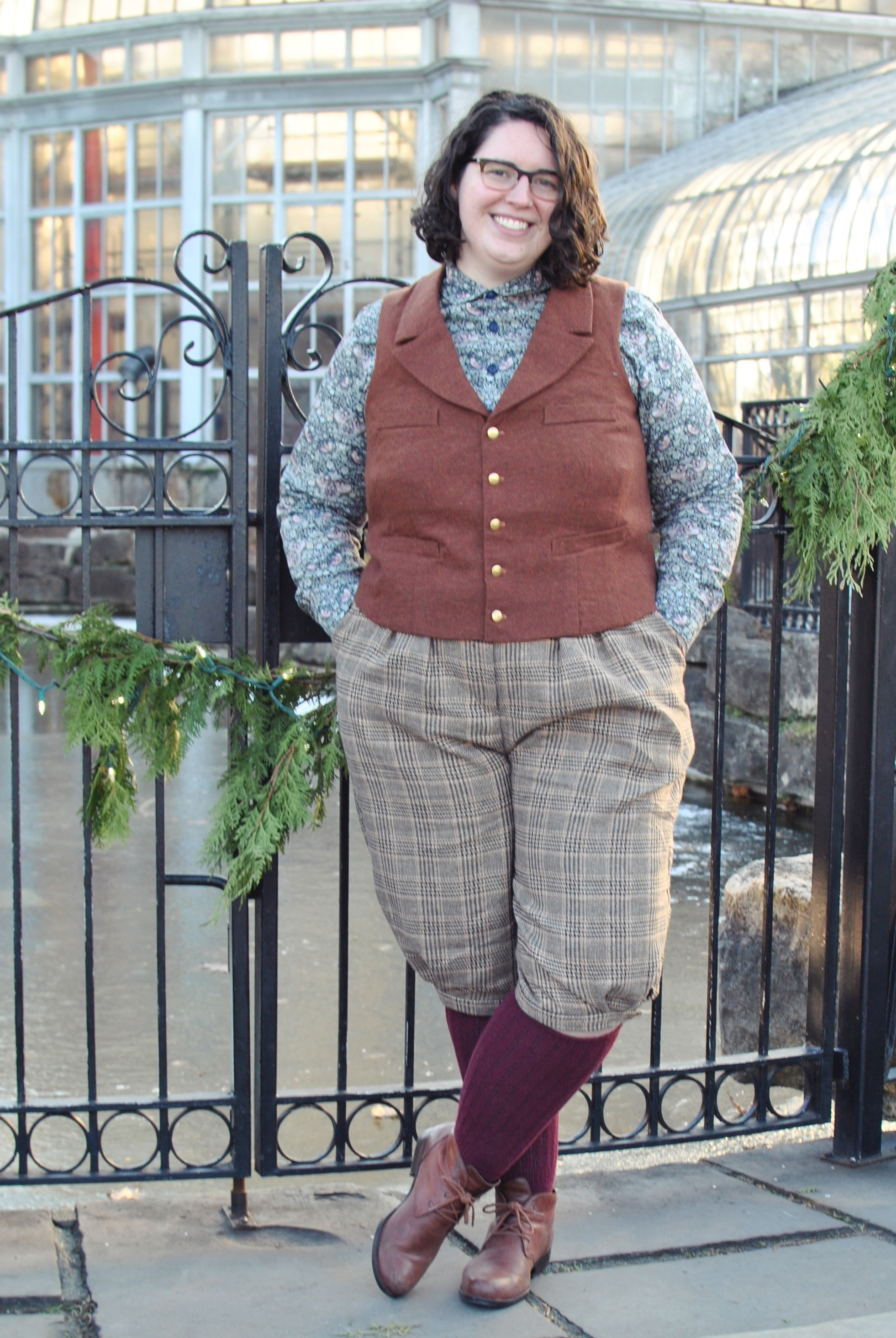 Shannon standing outdoors in front of greenhouse, wearing plaid knickerbockers, a rust wool vest, and a patterned shirt. Her legs are crossed and her hands in her pockets.