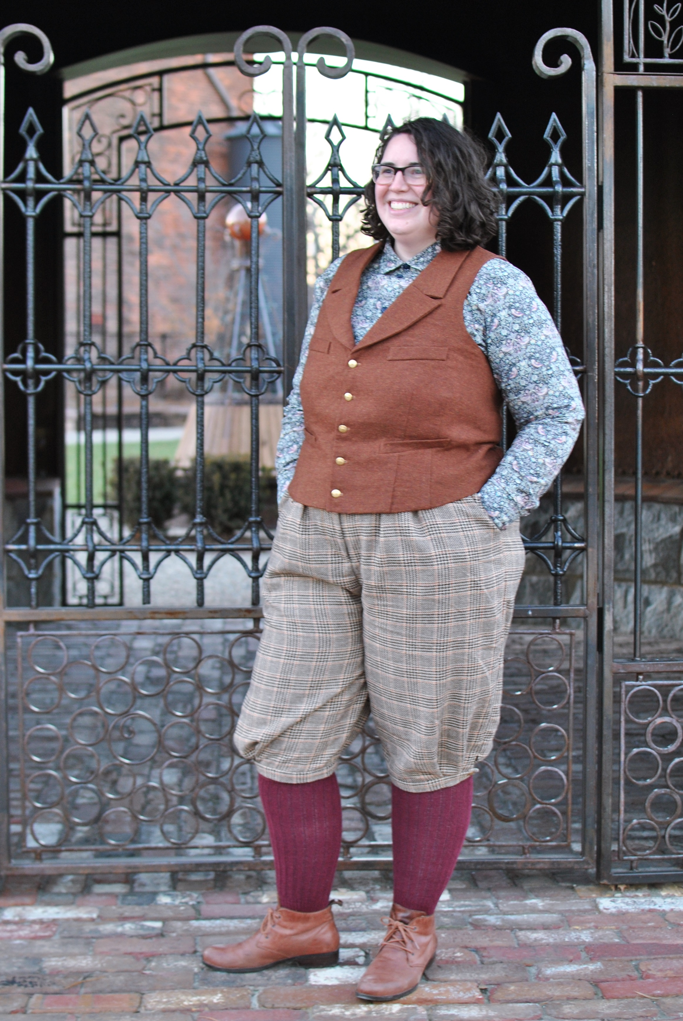 Shannon standing outdoors in front of an iron gate, wearing plaid knickerbockers, a rust wool vest, and a patterned shirt.